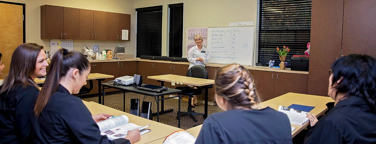 dental assisting students at desks learning from instructor